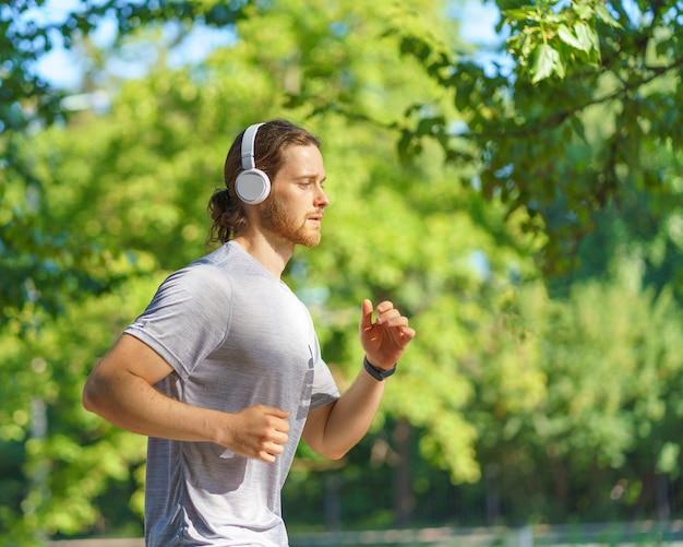 朝の緑豊かな公園でジョギングヘッドフォンを身に着けている若い男性スポーツマン