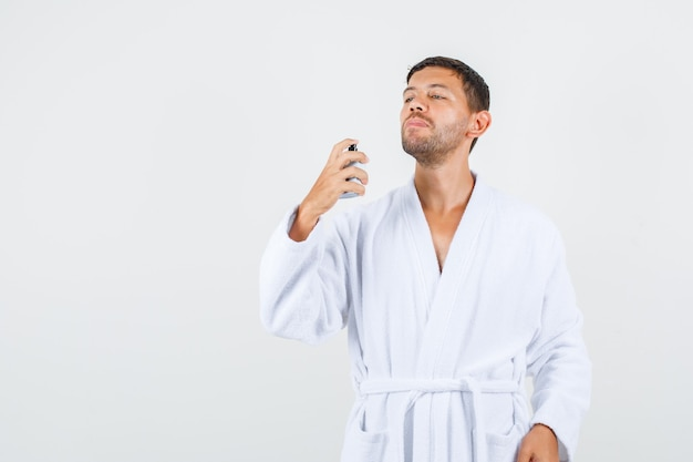 Giovane maschio che spruzza profumo in accappatoio bianco e sembra fiducioso, vista frontale.