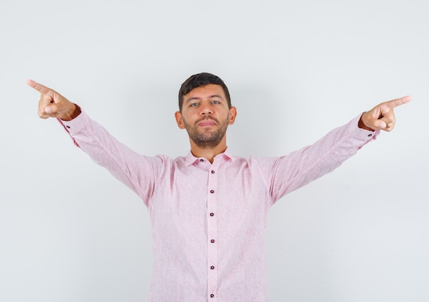Young male spreading arms and pointing away in pink shirt and looking confident , front view.