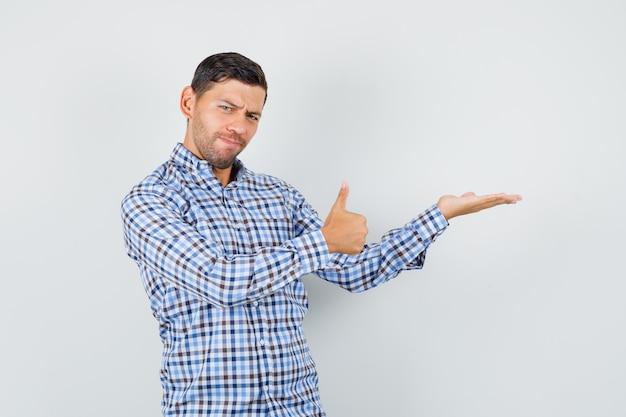若い男性が手のひらを脇に広げ、チェックシャツに親指を立てて自信を持って