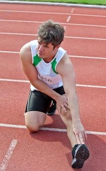 Молодой мужской спринтер, растягивающийся на полу перед гонкой на первой