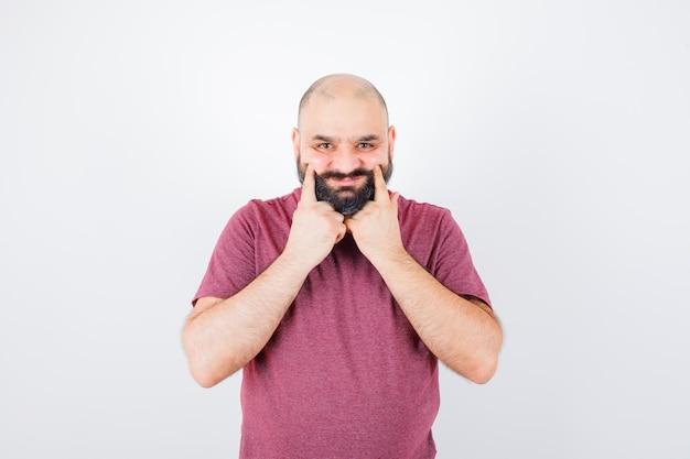 ピンクのtシャツで頬を絞る若い男性、正面図。