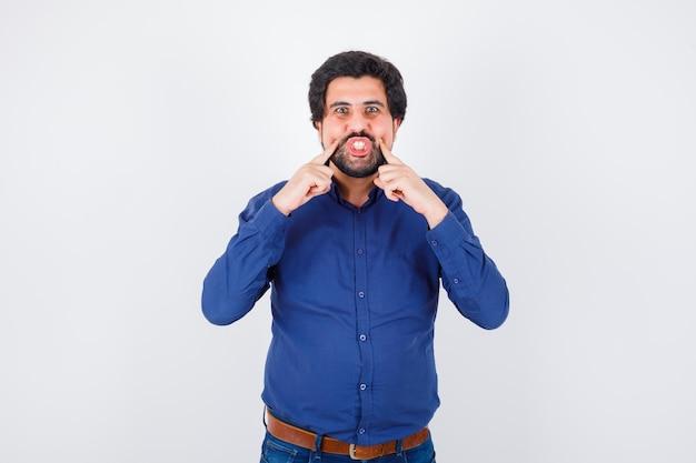 ロイヤルブルーのシャツの正面図で指で頬を絞る若い男性。