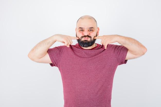 ピンクのtシャツの正面図で彼のパフ指を絞る若い男性。