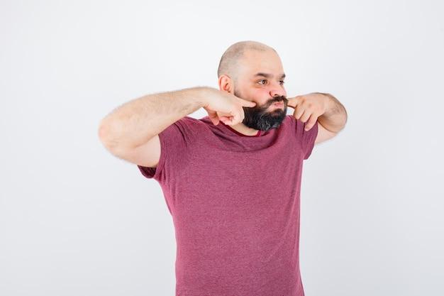 ピンクのtシャツで彼の膨らんだ指を絞る若い男性。
