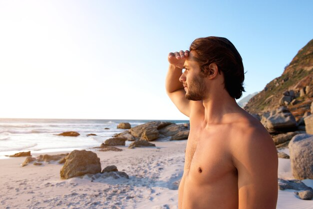 Young male standing at beach looking at water