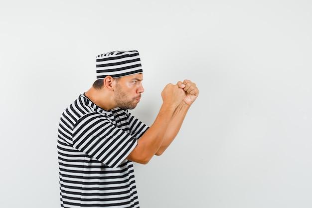Giovane maschio in piedi nella posa del pugile in cappello della maglietta a strisce e che sembra nervoso
