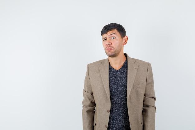 灰色がかった茶色のジャケット、黒いシャツで落ち着いて立っている若い男性と疑わしい、正面図。テキスト用のスペース