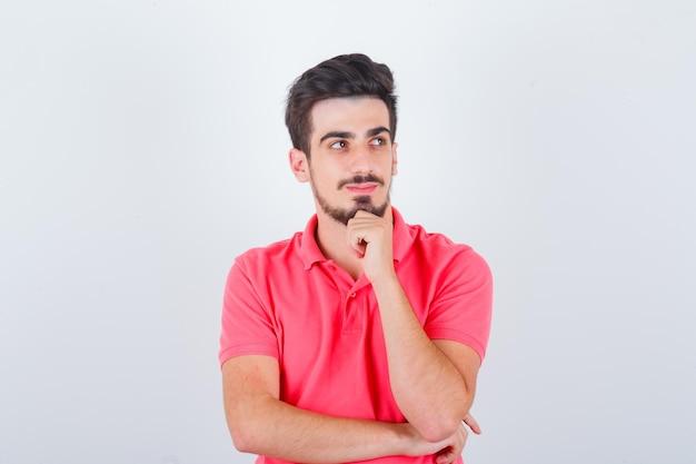 若い男性がtシャツを着てポーズを考えて立って、賢明な正面図を探しています。