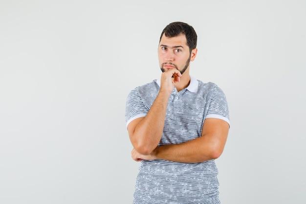 Giovane maschio in piedi in posa di pensiero in t-shirt e guardando sensato, vista frontale.