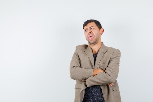 灰色がかった茶色のジャケットを着て腕を組んで立っていて、うんざりしているように見える若い男性。正面図。テキスト用のスペース