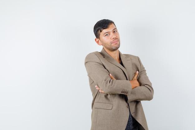 灰色がかった茶色のジャケット、黒のシャツを着て腕を組んで立っている若い男性と落ち着いて見えます。正面図。あなたのテキストのための空きスペース