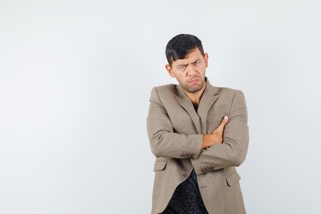 灰色がかった茶色のジャケット、黒のシャツで腕を組んで立って、気分を害したように見える若い男性、正面図。あなたのテキストのための空きスペース