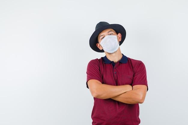 빨간 셔츠, 흰색 마스크에 팔짱을 끼고 불만을 품은 젊은 남성. 전면보기.