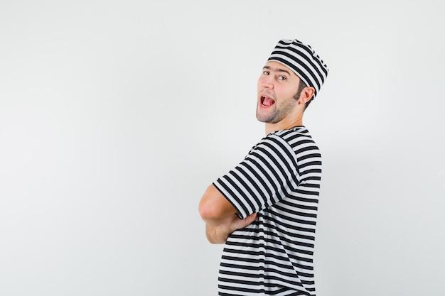 T- 셔츠, 모자에 교차 팔으로 서 젊은 남성과 자신감을 찾고.