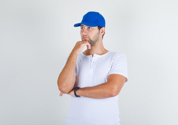 白いtシャツと青い帽子のあごに手で立っている若い男性