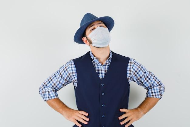 셔츠, 조끼, 모자, 마스크에 허리에 손으로 서 젊은 남성과 자신감, 전면보기를 찾고.