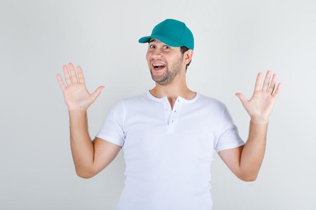 Молодой мужчина, стоящий с поднятыми открытыми руками в белой футболке и кепке, выглядит радостным