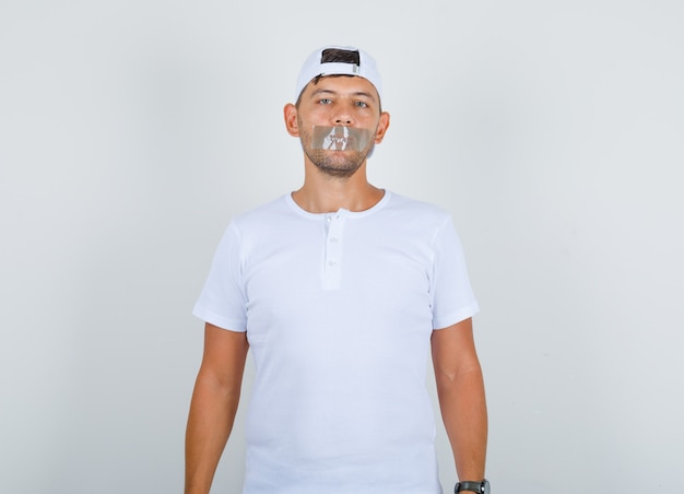 Young male standing with taped mouth in white t-shirt, cap and looking calm, front view.