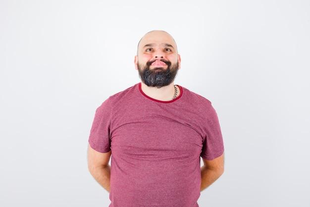 Giovane maschio che tira fuori la lingua mentre alza lo sguardo in una maglietta rosa e sembra strano. vista frontale.
