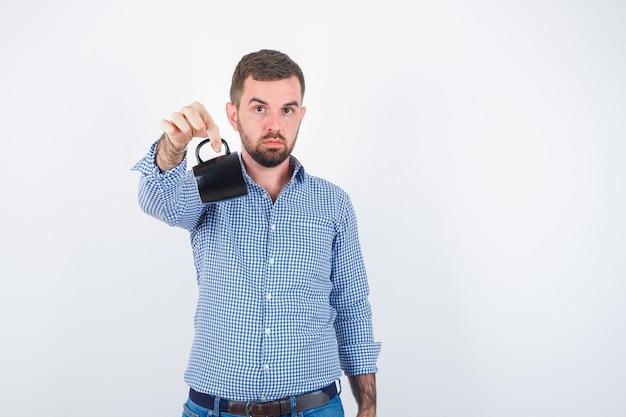젊은 남성 셔츠, 청바지에 컵의 핸들을 잡고 자신감을 찾고있는 동안 팔을 스트레칭. 전면보기.