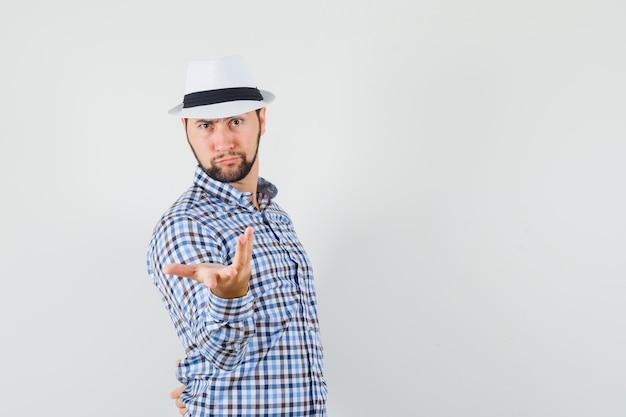 チェックシャツ、帽子、正面図で困惑したジェスチャーで手を伸ばす若い男性。