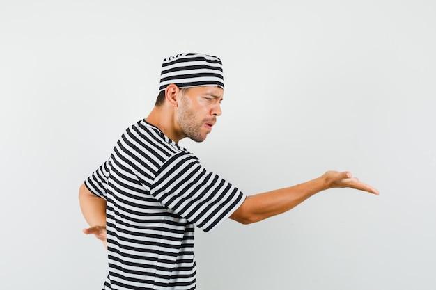 Молодой мужчина вопросительно протягивает руку в полосатой футболке и выглядит сердитым