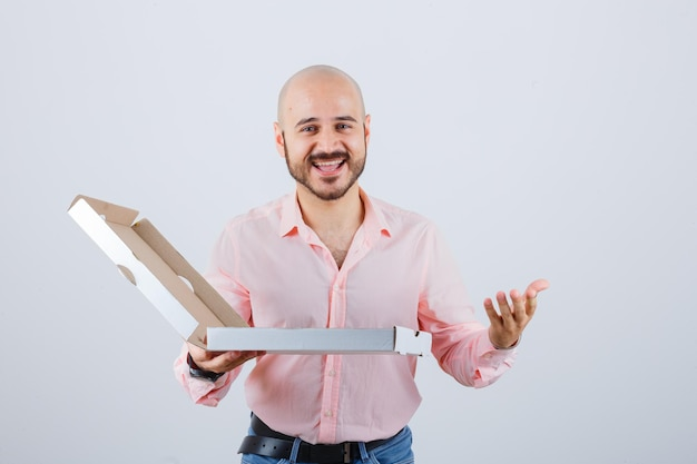 Giovane maschio che allunga la mano nel gesto interrogativo in camicia, jeans e guardando beato, vista frontale.