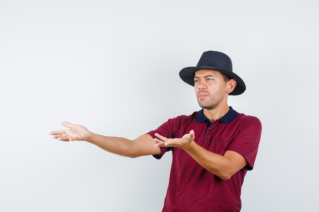 Young male stretching hands in disapproval gesture in t-shirt, hat , front view.