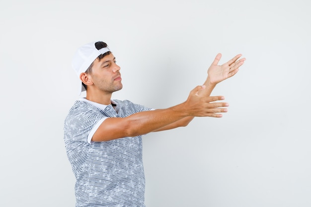 Young male stretching hands to find fault in t-shirt and cap