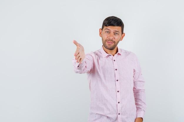 ピンクのシャツの正面図で振るために手を伸ばしている若い男性。