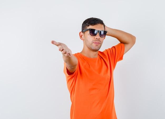 Молодой мужчина протягивает руку в оранжевой футболке и выглядит уверенно