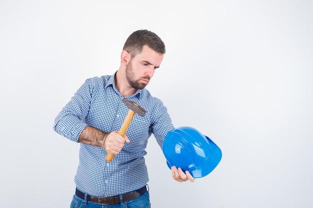 Giovane maschio colpisce il casco con un martello in camicia, jeans, casco e sembra serio, vista frontale.