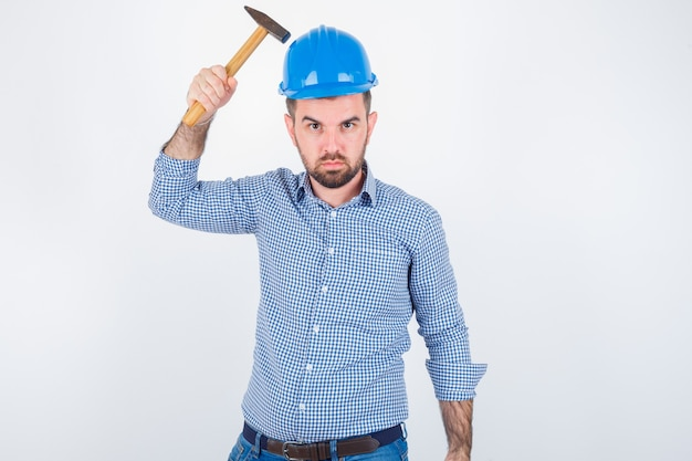 Young male striking his head with a hammer in shirt, jeans, helmet and looking stupid , front view.