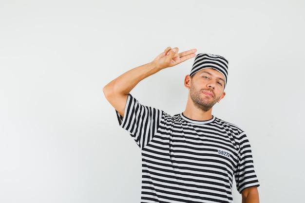 Giovane maschio in cappello a strisce della maglietta che gesturing con la mano e le barrette e che sembra fiducioso