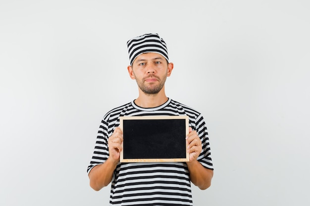 Young male in striped t-shirt hat holding blackboard and looking calm