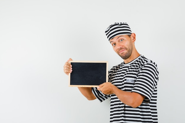 Young male in striped t-shirt hat holding blackboard and looking merry