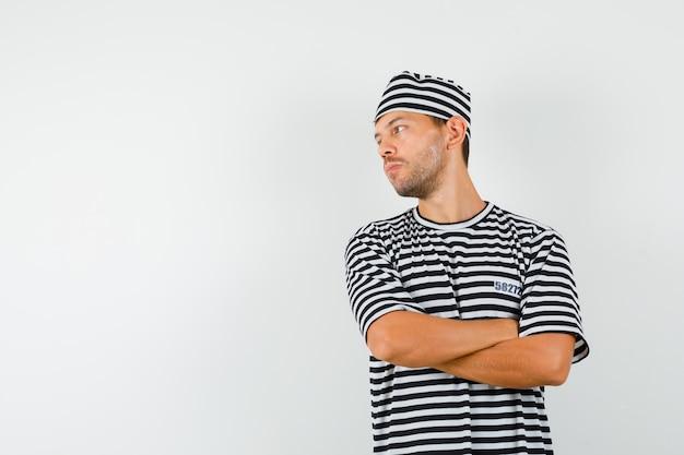 Giovane maschio in cappello della maglietta a strisce che osserva da parte con le braccia incrociate e che osserva messo a fuoco