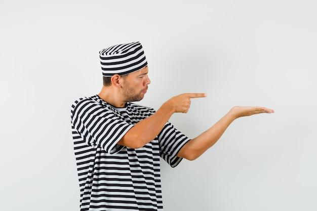 Giovane maschio in cappello della maglietta a strisce che indica la sua diffusione del palmo e che osserva messo a fuoco