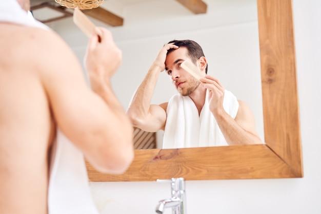 鏡のそばに立っている間彼の髪をなでる若い男性