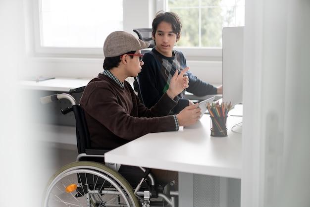 コンピューターで作業している車椅子の若い男子学生