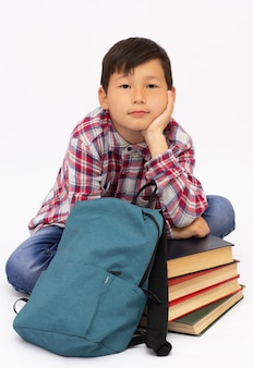 Young male student is sitting on the floor, reading a book