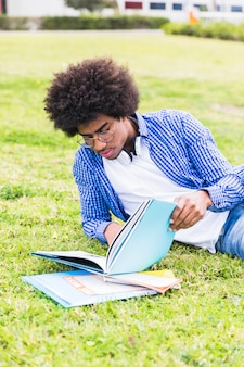Young male student leaning on lawn reading the book
