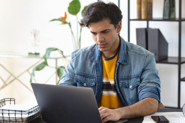 Young male student using laptop watching webinar or training, studying online at home, e-learning concept