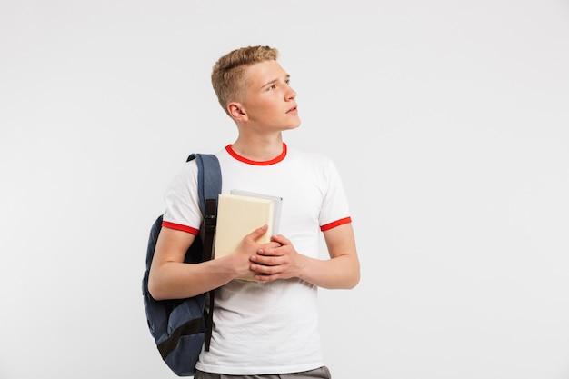 Молодой мужчина студент носить рюкзак, глядя в сторону на copyspace с задумчивым взглядом, держа книги, изолированные на белом