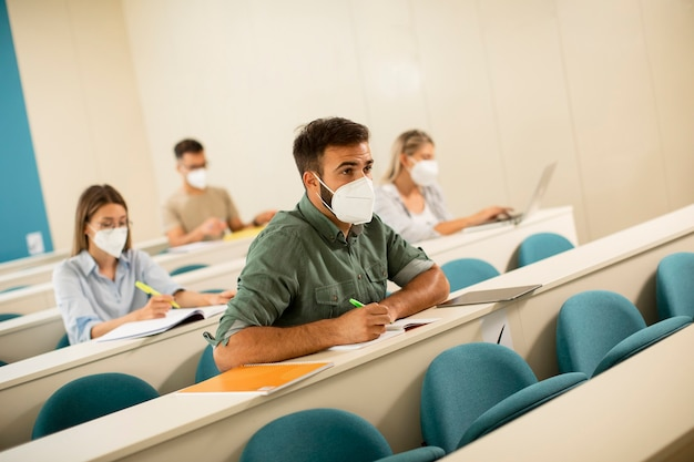講堂でウイルス対策のための顔面保護医療マスクを身に着けている若い男子学生