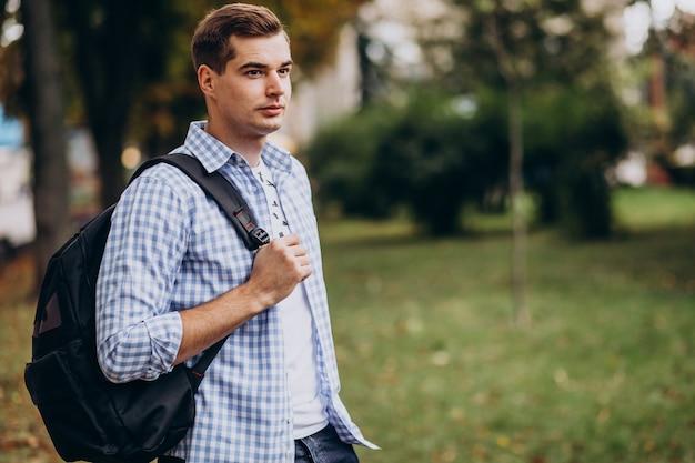公園を歩いているバッグを持つ若い男子学生
