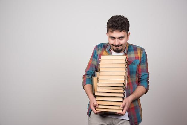 Giovane studente maschio con una pila di libri in posa per la telecamera.