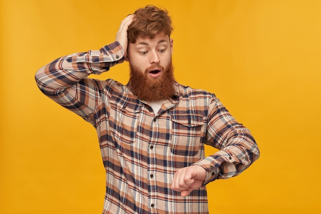 Young male student, with red hair and big beard, looks at his watches, keeps his hand on head and think about that he is late at work