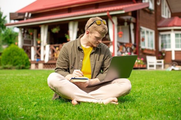 ノートパソコンとノートパソコンで屋外で勉強している若い男性。オンラインでビデオを見ている魅力的な男性、教育ウェビナー、ハイテク機器のトレーニングコース、日記にメモを書きます。教育、eラーニングの概念